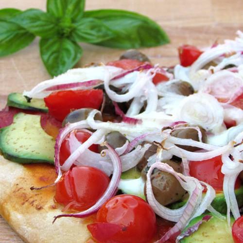 Pizza con avocado, pomodorini, cipolla, olive